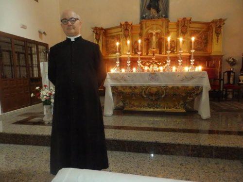 padre fortea frente al altar con sotana