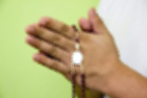 manos con un rosario