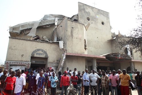 People stand in front of the partially destroyed St Theresa Catholic Church after a bomb blast in the Madala Zuba district of Nigeria's capital Abuja on December 25, 2011. Two explosions near churches during Christmas Day services in Nigeria, including one outside the country's capital, killed at least 28 people amid spiralling violence blamed on an Islamist group. The suspected attacks stoked fear and anger in Africa's most populous nation, which has been hit by scores of bombings and shootings attributed to Islamist group Boko Haram, with authorities seemingly unable to stop them. AFP PHOTO / Sunday Aghaeze
