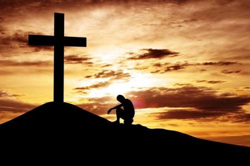 hombre al atardecer orando en una cruz