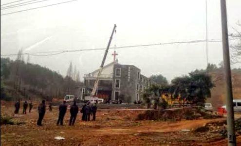 autoridades chinas quitando una criz de una iglesia