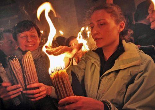 mujeres encendiendo velas con fuego santo