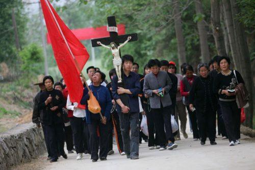 chinos en procesion con cruz de cristo