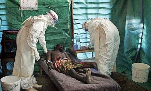 paciente con signos de ebola en cama con medicos visitandolo
