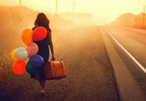 mujer camina con globos y maleta