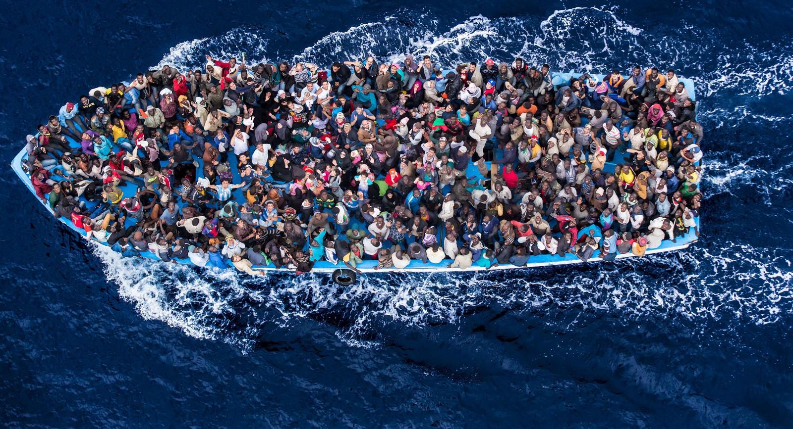 barcaza con migrantes musulmanes fondo