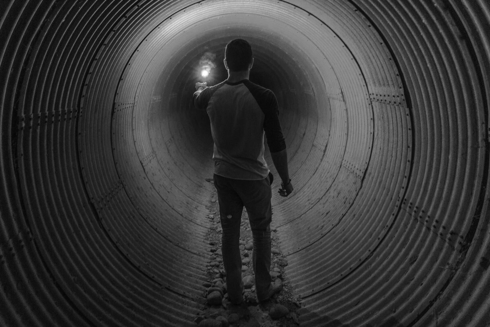 hombre en un tunel iluminado con una vela fondo