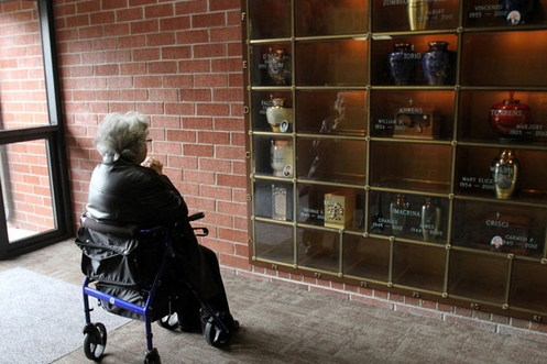 mujer orando frente a un urnario