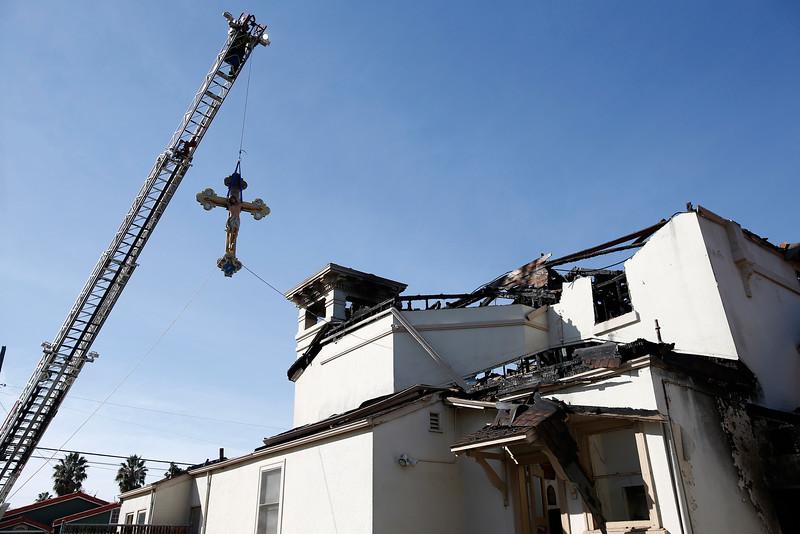 bomberos removiendo la cruz de la iglesia de san jose incendiada