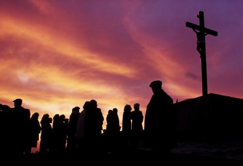 gente al atardecer ante una cruz