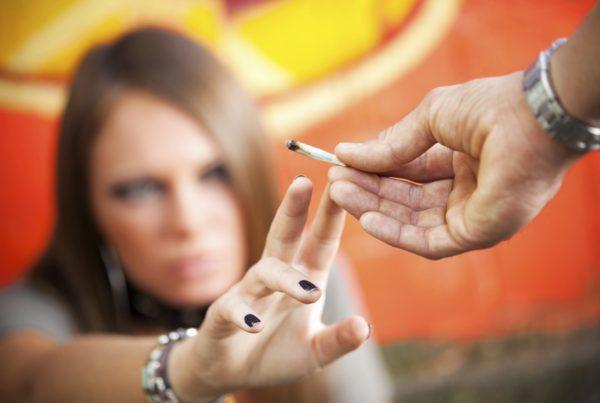 hombre le da un porro de marihuana a una mujer fondo