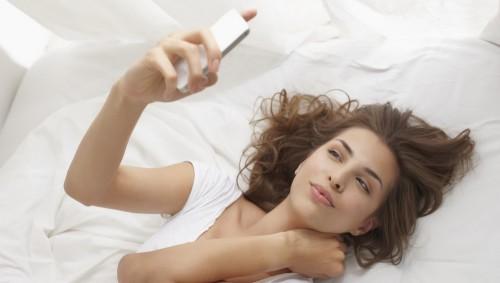 mujer con selfie en la cama