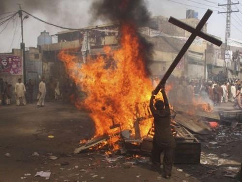 musulman destruyendo una cruz