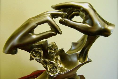 escultura de manos poniendose un anillo fondo