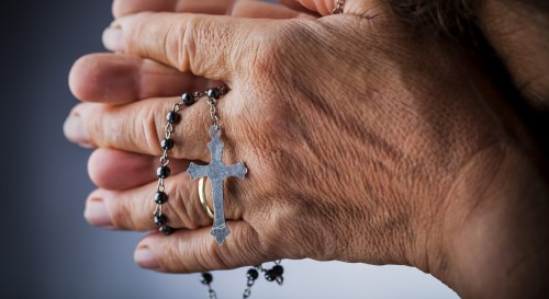 manos de mujer con rosario orando fondo