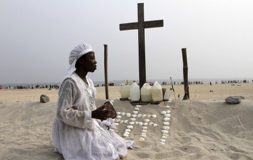 mujer nigeriana ante cruz cristiana