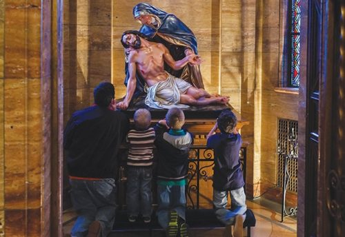 padre e hijos mirando estatua de descendimiento