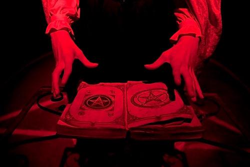 satanista con un libro satanico