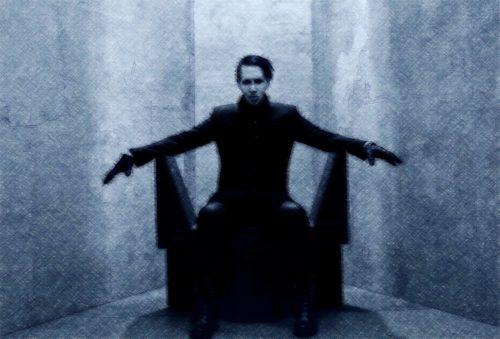 anticristo vestido de negro sentado