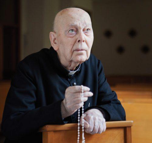 amorth arrodillado rezando el rosario