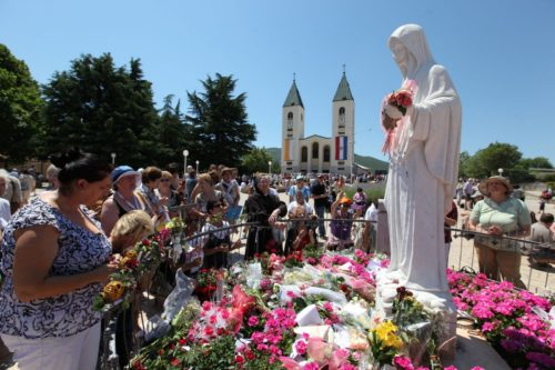 peregrinos llevan flores a estatua de medjugorje